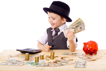 young boy dressed as banker counts stacks of dollars and coins