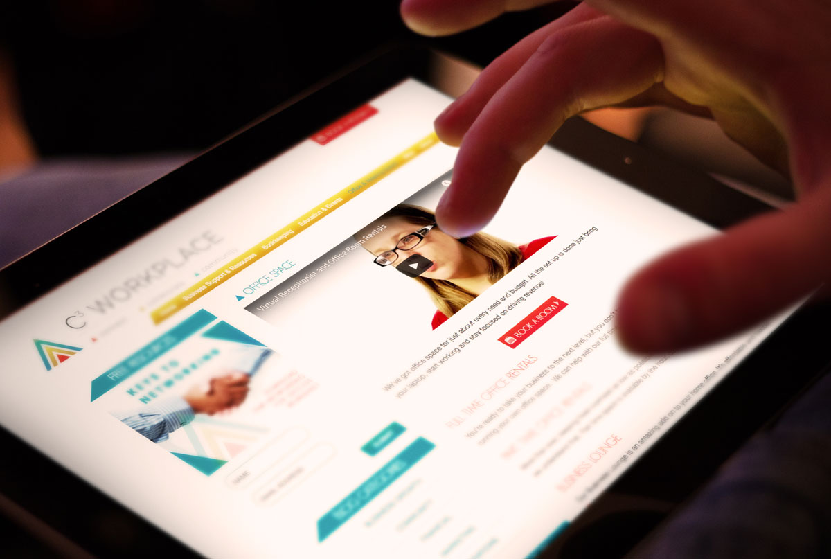 Close up of fingers pinching tablet displaying C3 Workplace website