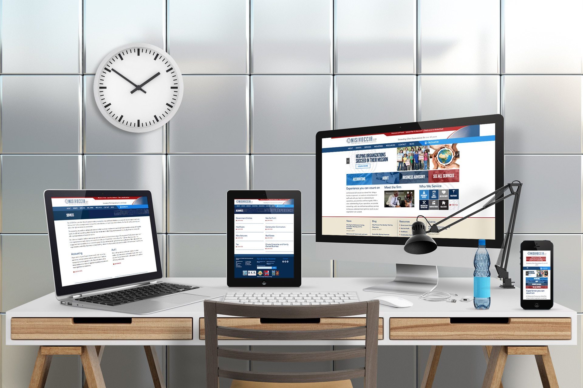 desk displaying computer, laptop, tablet and smartphone featuring Nisivoccia website