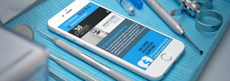 smartphone displaying 50 Commerce Dental website next to various dental tools