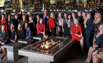 large group of women sitting around fire pit in urban setting