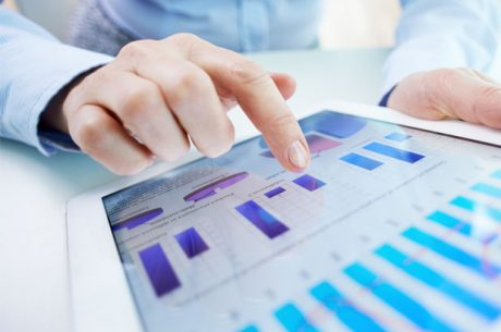 Woman pointing to charts on tablet