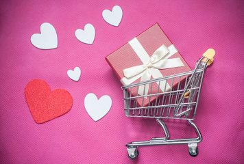 Miniature shopping cart with gift box and hearts. Concept Valentine's Day Marketing