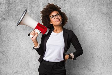 Business woman considering message while holding a megaphone