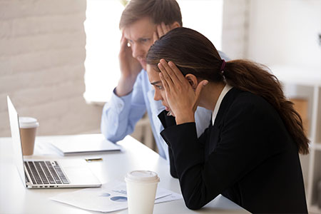 Business woman and man looking at computer screen frustrated about a marketing mistake