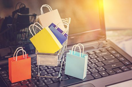 Small shopping cart with colorful bags sitting on top of an open laptop for wordpress ecommerce shopping