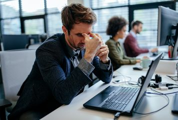 Frustrated man sitting in their office in front of his laptop