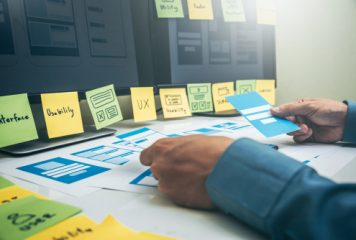 Accessibility UX design elements being structured by designer using design templates in front of a computer with some layouts on sticky notes and cards on the table