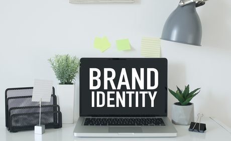 Brand Identity projected on a laptop screen sitting on a office desk with miscellaneous office supplies