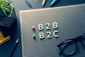 B2B and B2C letters, push pins and eyeglasses on a peg letter board on top of a desk with pens, paper clips and an indoor plant