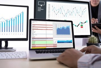 Employee using Google analytics on multiple computers to pull data and graphs