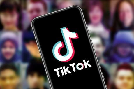TikTok app open on a mobile phone with people's profiles blurred in background.