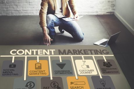 Employee sitting near floor with elements of content marketing displayed through icons