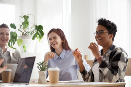 Three employees sitting in a conference room laughing