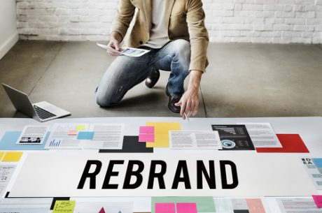 Man learning how to rebrand an organization by sitting near computer and scattered design papers on the floor with rebrand written across the sheets.