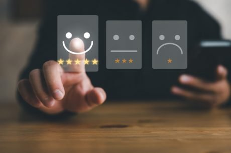 Man using cell phone social media to rate customer experience from good to bad and selecting good smiley face