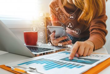 Woman holding phone with digital marketing concept icons infront of a laptop and pointing to a chart on a paper