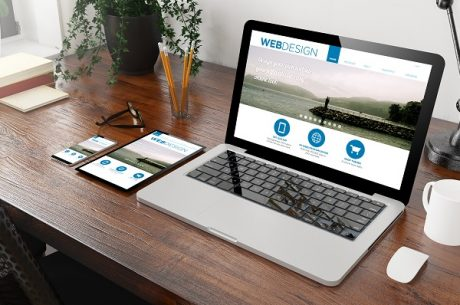 Web design site on a laptop screen beside a cellphone and an iPad on top of office table