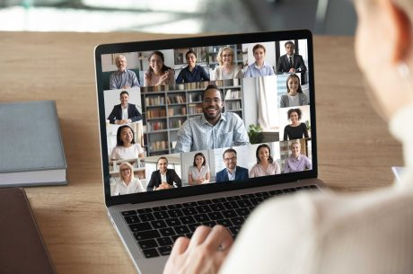 Woman infront of a laptop with people on screen attending virtual business networking event