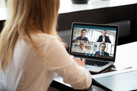 Woman in front of laptop speaking with four people at a virtual event