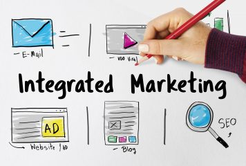 Integrated Marketing text with email, website, blog and SEO icons and a hand writing viral video